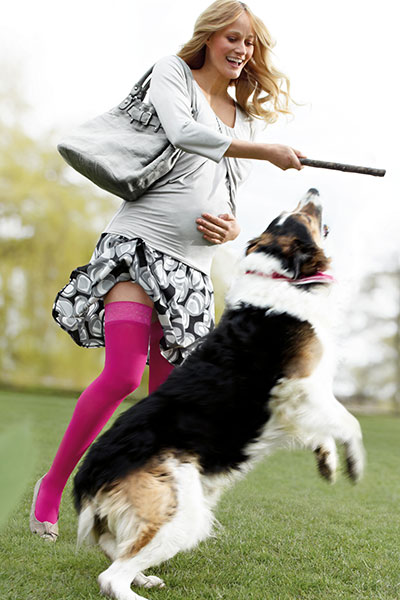 Lady wearing pink compression stockings playing with dog